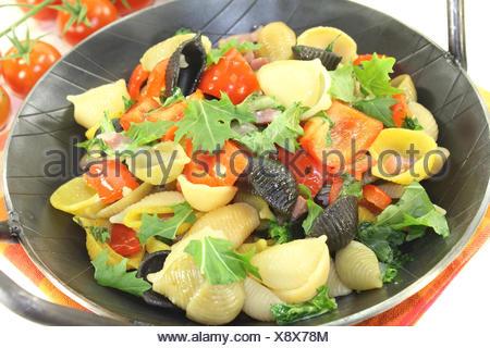 Nudelpfanne mit Paprika, Tomaten und Knoblauch vor hellem Hintergrund - Stock Photo