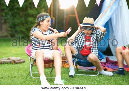 Girl and two brothers eating ice lollies in front of homemade tent in garden - Stock Photo