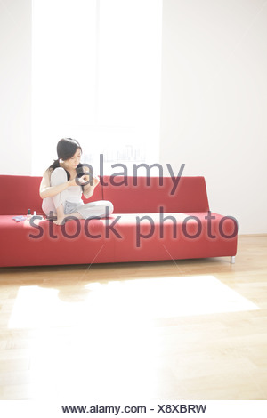 Young woman sitting on a couch and filing her fingernails - Stock Photo