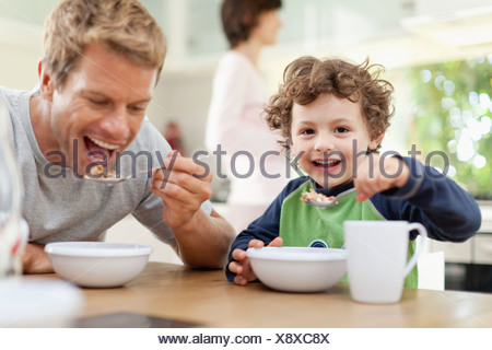Father and son eating breakfast - Stock Photo