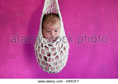 Newborn baby, five days, suspended in a 'stork's bag' - Stock Photo