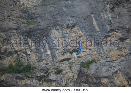 An unidentified person doing stunts with a parawing in front of a huge rock face.  Lauterbrunnen, Switzerland. - Stock Photo