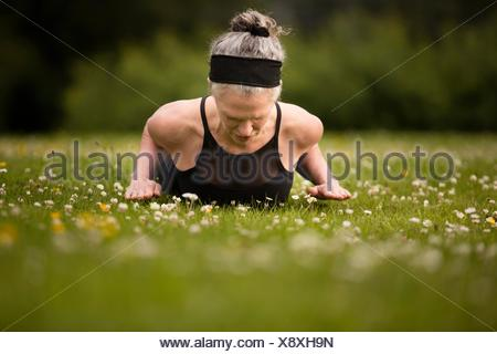 Mature woman practicing yoga cobra pose in field - Stock Photo