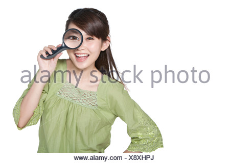 Portrait of Young Woman Looking Through Magnifying Glass - Stock Photo