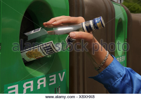 Close-up of a hand putting an empty bottle into a re-cycling bin. - Stock Photo