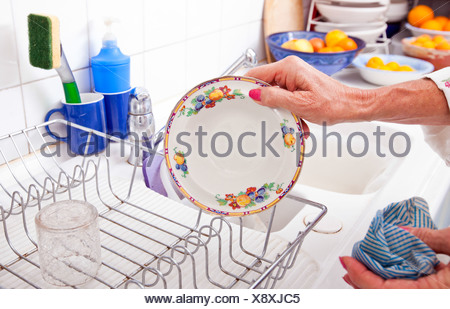 Cropped image senior woman arranging plate rack kitchen counter - Stock Photo