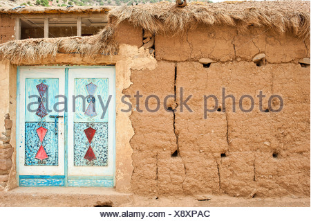 Facade made of adobe bricks, typical ornamental metal door, painted, Ait Bouguemez Valley, High Atlas Mountains, Morocco, Africa - Stock Photo