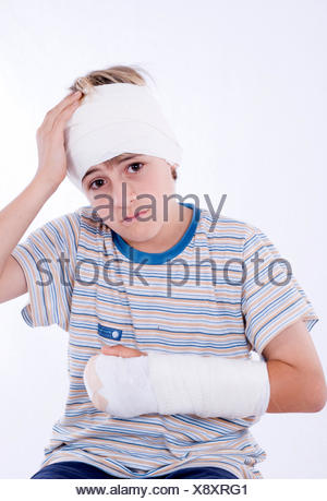 boy with arm in plaster and bandage on head - Stock Photo