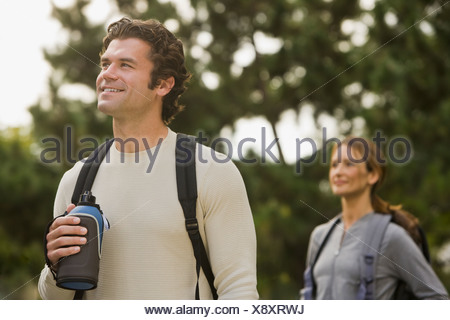 Couple wearing backpacks in woods - Stock Photo