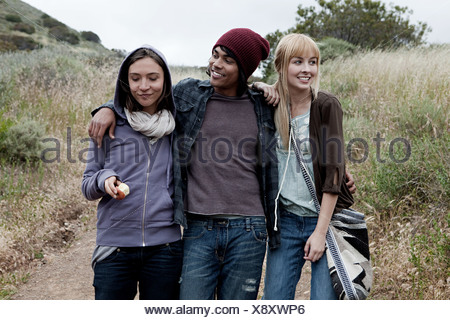 Group of young friends walking along path - Stock Photo