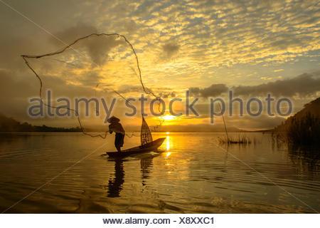 Silhouette of a man throwing fishing net, Lake Bangpra, Thailand - Stock Photo
