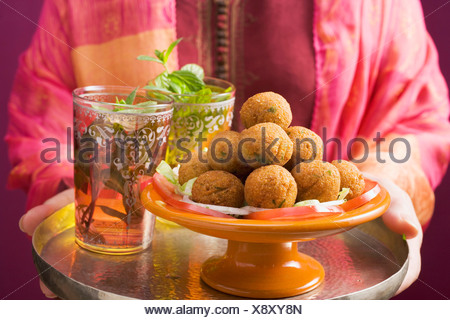 Woman holding tray of falafel (chick-pea balls) and tea - - Stock Photo