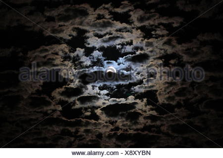 Moon Behind Clouds At Night - Stock Photo