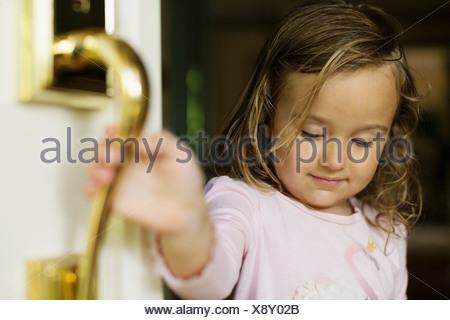 Female toddler opening door - Stock Photo