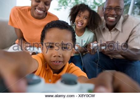 Family playing video games console on sofa at home smiling front view differential focus - Stock Photo