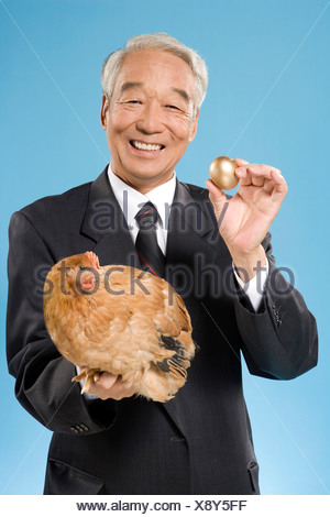 Businessman Holding A Chicken And Golden Egg - Stock Photo