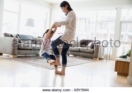 Daughter dancing on mothers feet in living room - Stock Photo