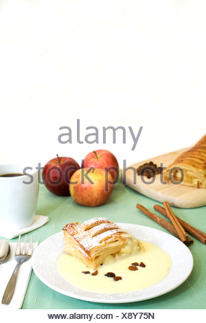 Apple strudel with custard, a cup of coffee, apples, cinnamon sticks and raisins - Stock Photo
