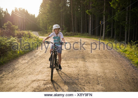Sweden, Vastergotland, Lerum, Slatthult, Boy (10-11) on bicycle outdoors - Stock Photo