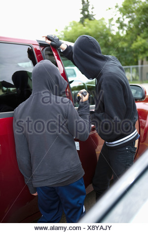 two young men in hoods breaking into a vehicle; edmonton, alberta, canada - Stock Photo