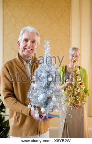 Senior couple with ornamental Christmas trees, smiling, portrait, close-up of man - Stock Photo