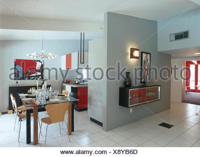 Plywood chairs at glass table in modern open plan kitchen dining room - Stock Photo