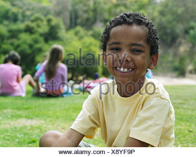 Boy 7 9 sitting on grass in park smiling portrait focus on foreground - Stock Photo
