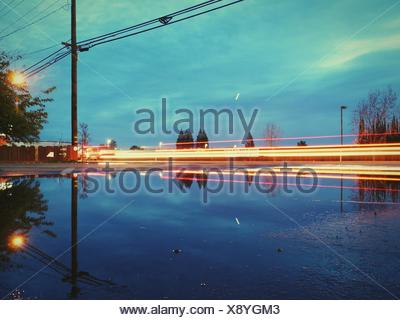 Reflection Of Light Trails And Electricity Pylon In Puddle - Stock Photo