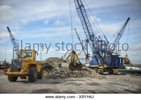 Crane and digger loading recycled glass onto ships - Stock Photo