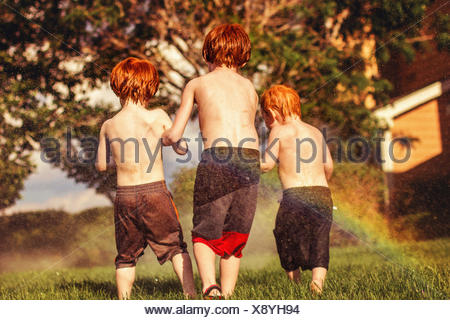 Three young brothers playing in water sprinklers - Stock Photo