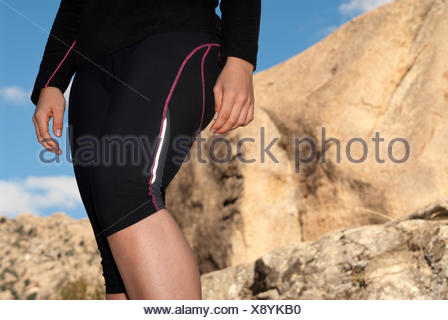 young runner woman legs close-up on outdoor background - Stock Photo