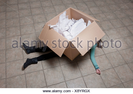 Teenage girl lying under cardboard box - Stock Photo