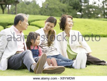 Three-generation family sitting on grass - Stock Photo