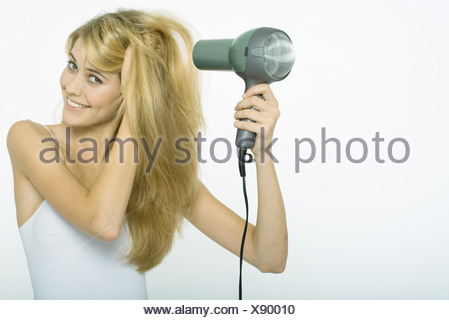 Teenage girl blow-drying hair, smiling at camera - Stock Photo
