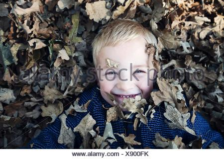 Overhead view of boy lying down covered in autumn leaves looking at camera smiling - Stock Photo