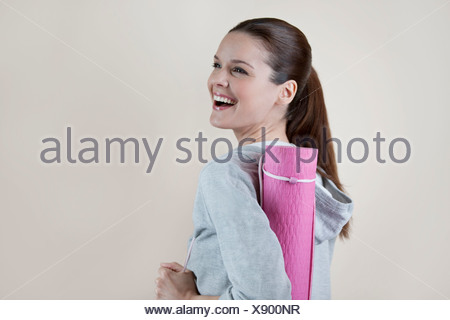 A young woman carrying a yoga mat, laughing - Stock Photo