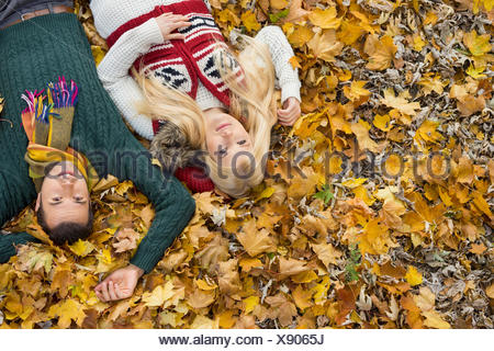 High angle portrait of young couple lying on autumn leaves at park - Stock Photo