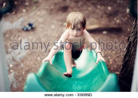 Boy climbing up a slide - Stock Photo