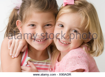 Two young sisters hugging and smiling - Stock Photo