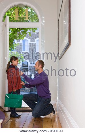 A father doing up his daughters coat - Stock Photo