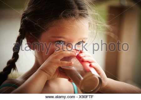 Close up of girl with braids drinking chocolate milk - Stock Photo
