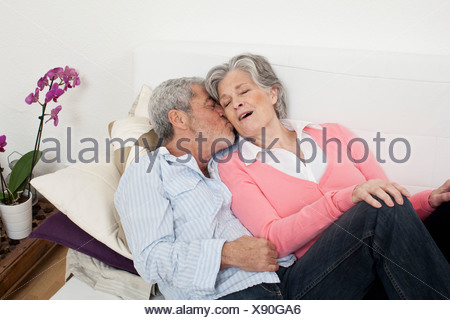 A senior man and senior woman lying on a couch together - Stock Photo