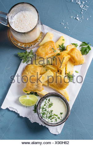Traditional british fast food fish and chips. Served with white cheese sauce, lime, parsley, glass of lager beer on white paper over blue concrete bac - Stock Photo
