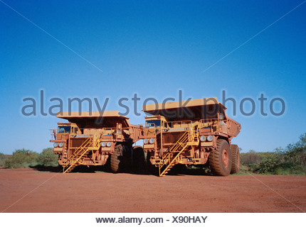 Two large dump trucks side by side - Stock Photo