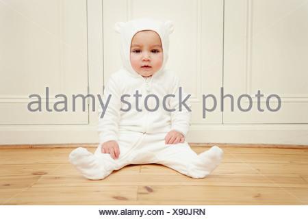 Baby sitting wearing bear babygro - Stock Photo