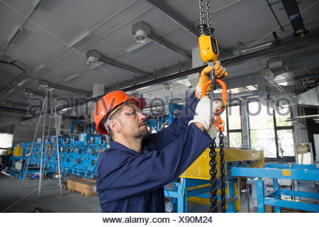 Worker adjusting chain hoist in industrial plant - Stock Photo