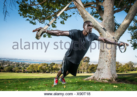 Young man training with lunge rope in field - Stock Photo