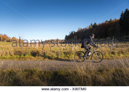 Sweden, Vastergotland, Lerum, Mature man riding bicycle on dirt road among pastures and forests - Stock Photo