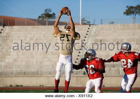 Opposing American football players competing for ball during competitive game, offensive receiver catching ball in mid-air - Stock Photo