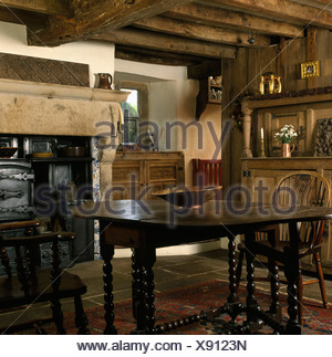 Windsor chairs and Jacobean oak table with barley-twist legs in beamed country dining room with old cast-iron range in fireplace - Stock Photo